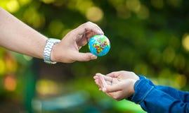 Άτομο που δίνει τη γήινη σφαίρα στο μικρό κορίτσι Στοκ Φωτογραφία