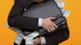 Άτομο που αγκαλιάζει το χαρτοφύλακά του με να κολλήσει έξω τα χρήματα, δωροδοκία, δωροδοκία, κινηματογράφηση σε πρώτο πλάνο φιλμ μικρού μήκους
