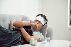 Άτομο που αισθάνεται κακό να βρεθεί στον καναπέ και το βήξιμο στοκ εικόνα με δικαίωμα ελεύθερης χρήσης