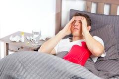 Άτομο που αισθάνεται κακό να βρεθεί στο κρεβάτι και το βήξιμο στοκ φωτογραφία