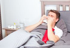 Άτομο που αισθάνεται κακό να βρεθεί στο κρεβάτι και το βήξιμο στοκ εικόνες