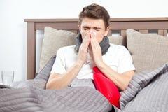 Άτομο που αισθάνεται κακό να βρεθεί στο κρεβάτι και το βήξιμο στοκ εικόνα