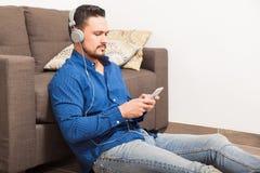 Άτομο που ακούει τη μουσική που χρησιμοποιεί τα ακουστικά Στοκ εικόνα με δικαίωμα ελεύθερης χρήσης