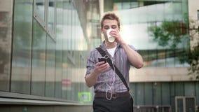 Άτομο που ακούει τον καφέ μουσικής και κατανάλωσης περπατώντας φιλμ μικρού μήκους