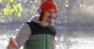 Άτομο που ακούει το χορό μουσικής κοντά στην υπαίθρια ανατολή δέντρων, πάρκο φθινοπώρου πρωινού ακουστικών ένδυσης αθλητικών τύπω φιλμ μικρού μήκους