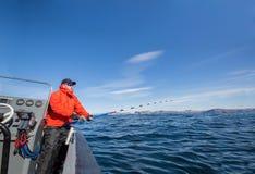 Άτομο που αλιεύει από μια βάρκα με την περιστροφή Κόκκινο σακάκι αθλητισμός glasse Στοκ Φωτογραφίες
