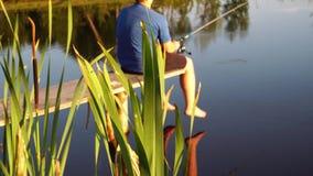 Άτομο που αλιεύει στη λίμνη στο ηλιοβασίλεμα φιλμ μικρού μήκους