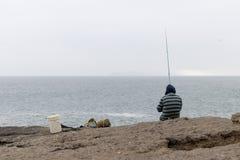 Άτομο που αλιεύει στον απότομο βράχο στοκ εικόνες
