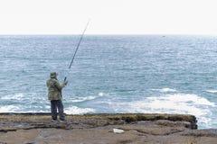 Άτομο που αλιεύει στον απότομο βράχο στοκ φωτογραφίες με δικαίωμα ελεύθερης χρήσης