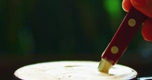 Άτομο που αναμιγνύει επάνω το foamy καφέ φιλμ μικρού μήκους