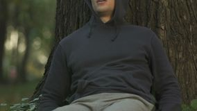 Άτομο που αναπνέει και που κάθεται μετά βίας κάτω από το δέντρο, αίσθημα άρρωστο, προβλήματα με την καρδιά φιλμ μικρού μήκους