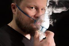 Άτομο που αναπνέει μέσω nebulizer της μάσκας στοκ φωτογραφίες