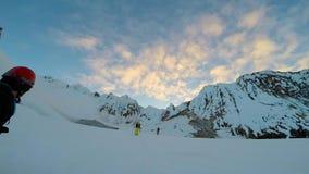 Άτομο που αναρριχείται επάνω στο χιονώδη τσεκούρι και τα σκυλιά έλκηθρου πάγου βουνών απόθεμα βίντεο