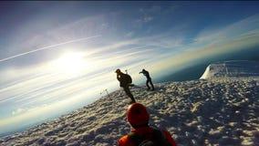 Άτομο που αναρριχείται επάνω στο χιονώδη τσεκούρι και τα σκυλιά έλκηθρου πάγου βουνών φιλμ μικρού μήκους