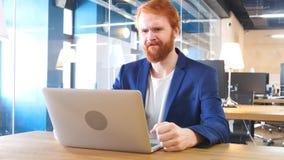 Άτομο που ανατρέπεται από την απώλεια, που λειτουργεί στο lap-top Στοκ Εικόνες