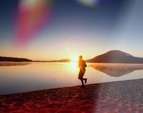 Άτομο που αντιτίθεται στην παραλία το σκηνικό ενός όμορφου ηλιοβασιλέματος Άμμος της λίμνης βουνών Στοκ Φωτογραφία
