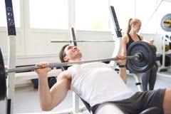 Άτομο που ανυψώνει το βάρος Barbell λαμπρά στη γυμναστική LIT Στοκ Εικόνα
