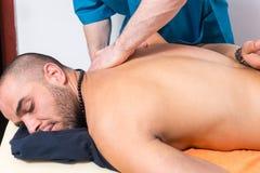 Άτομο που απολαμβάνει ένα πίσω μασάζ σε μια κλινική Στοκ Εικόνα