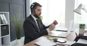 Άτομο που απολαμβάνει ακούοντας και τραγουδώντας τη μουσική στο γραφείο απόθεμα βίντεο