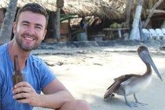 Άτομο που απολαμβάνει μια μπύρα στην παραλία στοκ εικόνες