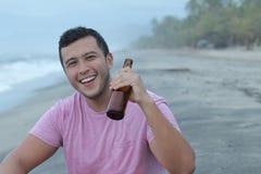 Άτομο που απολαμβάνει μια μπύρα στην παραλία στοκ φωτογραφίες
