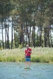 Άτομο που απολαμβάνει το γύρο στη λίμνη με το paddleboard Στοκ Εικόνες