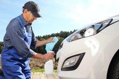 Άτομο που απομακρύνει τα έντομα από ένα αυτοκίνητο Στοκ Φωτογραφία
