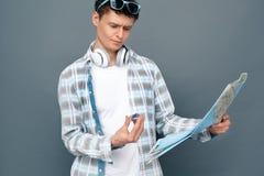 Άτομο που απομονώνεται στον γκρίζο τοίχων τουρισμού χάρτη εκμετάλλευσης έννοιας μόνιμο που εξετάζει την πυξίδα συγκεχυμένη στοκ φωτογραφία με δικαίωμα ελεύθερης χρήσης