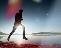 άτομο που ασκεί και που τεντώνει στην παραλία λιμνών στην ανατολή Υγιής τρόπος ζωής Μόνη νέα άσκηση ατόμων ικανότητας στο πρωί be Στοκ Εικόνες