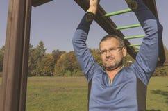 Άτομο που ασκεί σε ένα πλαίσιο αναρρίχησης στο πάρκο στοκ φωτογραφία με δικαίωμα ελεύθερης χρήσης