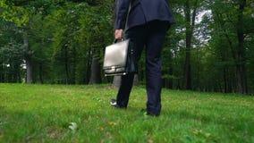 Άτομο που αφήνει το χαρτοφύλακα στη χλόη και που περπατά στο πράσινο δάσος, διαφυγή από την πίεση απόθεμα βίντεο