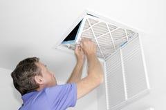 Άτομο που αφαιρεί το βρώμικο φίλτρο αέρα στοκ εικόνα με δικαίωμα ελεύθερης χρήσης