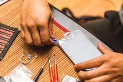 Άτομο που αφαιρεί το γυαλί οθόνης από το σπασμένο τηλέφωνο Στοκ Φωτογραφίες