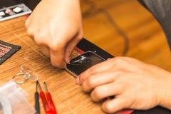 Άτομο που αφαιρεί το γυαλί οθόνης από το σπασμένο τηλέφωνο Στοκ Εικόνα