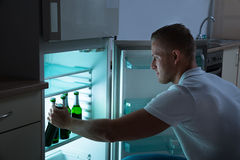 Άτομο που αφαιρεί το μπουκάλι μπύρας από το ψυγείο Στοκ εικόνα με δικαίωμα ελεύθερης χρήσης