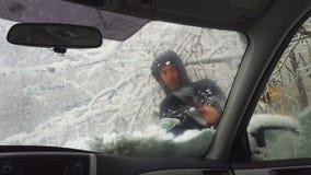 Άτομο που αφαιρεί το χιόνι από τον ανεμοφράκτη μετά από τις βαριές χιονοπτώσεις το χειμώνα 4K απόθεμα βίντεο