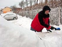 Άτομο που αφαιρεί το χιόνι από το αυτοκίνητο στοκ εικόνα με δικαίωμα ελεύθερης χρήσης