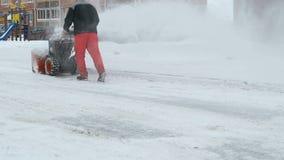 Άτομο που αφαιρεί το χιόνι με τη μηχανή αρότρων χιονιού απόθεμα βίντεο