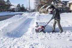 Άτομο που αφαιρεί το χιόνι με Snowblower μια ηλιόλουστη ημέρα 3 Στοκ Φωτογραφίες