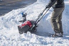 Άτομο που αφαιρεί το χιόνι με Snowblower μια ηλιόλουστη ημέρα Στοκ Εικόνες