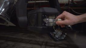 Άτομο που αλλάζει μια λάμπα φωτός αλόγονου στο στάδιο που ανάβει τον επαγγελματικό εξοπλισμό, 4K φιλμ μικρού μήκους