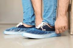 Άτομο που βάζει στις μπλε καλύψεις παπουτσιών στοκ εικόνα