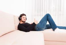 Άτομο που βάζει στον καναπέ που φορά τα ακουστικά που παρουσιάζουν αντίχειρα Στοκ φωτογραφία με δικαίωμα ελεύθερης χρήσης