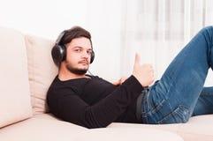Άτομο που βάζει στον καναπέ που φορά τα ακουστικά που παρουσιάζουν αντίχειρα Στοκ Φωτογραφίες