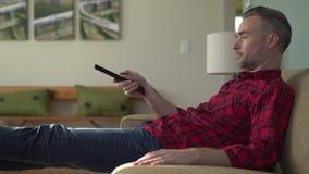Άτομο που βάζει στο σερφ καναλιών καναπέδων απόθεμα βίντεο
