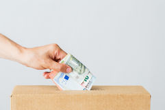 Άτομο που βάζει τα ευρο- χρήματα στο κιβώτιο δωρεάς Στοκ Φωτογραφίες