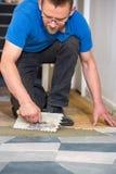 Άτομο που βάζει τα κεραμίδια πατωμάτων με την επικεράμωση trowel στοκ φωτογραφίες με δικαίωμα ελεύθερης χρήσης
