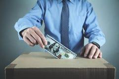 Άτομο που βάζει τα χρήματα στο κουτί από χαρτόνι τα χρήματα σώζουν Στοκ Εικόνα