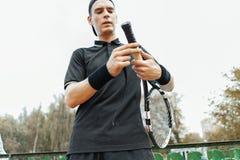 Άτομο που βάζει τη νέα ταινία πιασιμάτων στη ρακέτα αντισφαίρισης Τυλίγοντας ταινία λήξης στη ρακέτα στοκ εικόνες