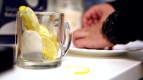 Άτομο που βάζει το λεμόνι σε ένα φλυτζάνι τσαγιού Πάρα πολλά λεμόνια φιλμ μικρού μήκους